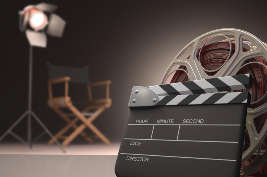 I forgrunden står en filmrulle og et klappetræ. I baggrunden står en stol og et lampe på et stativ.