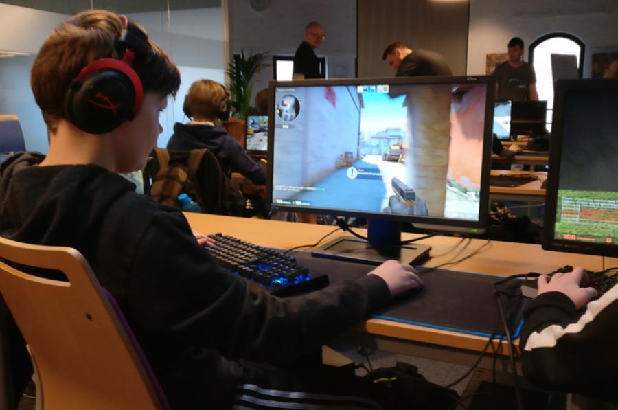 En dreng sidder ved en computer med ørebøffer og spiller et skydespil. I baggrunden sidder andre børn og spiller computerspil.