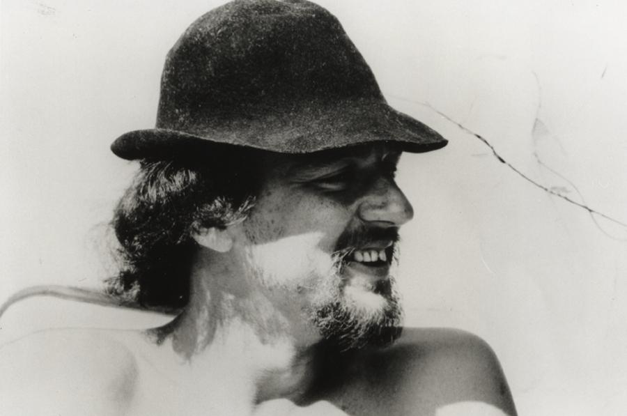 Et sort-hvidt portræt foto af Ole Lund Kirkegaard. Han kigger ud til siden med en hat på hovedet.