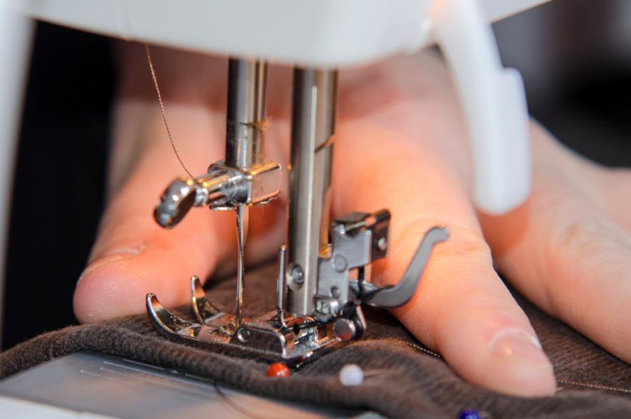En hånd holder på noget stof og syr på en symaskine.