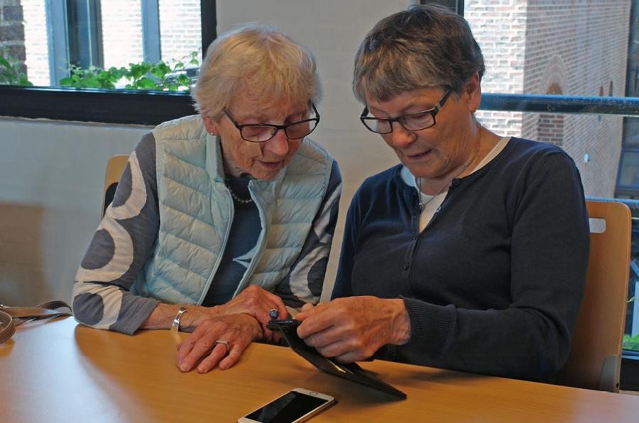 To kvinder sidder ved siden af hinanden og kigger på en mobiltelefon.