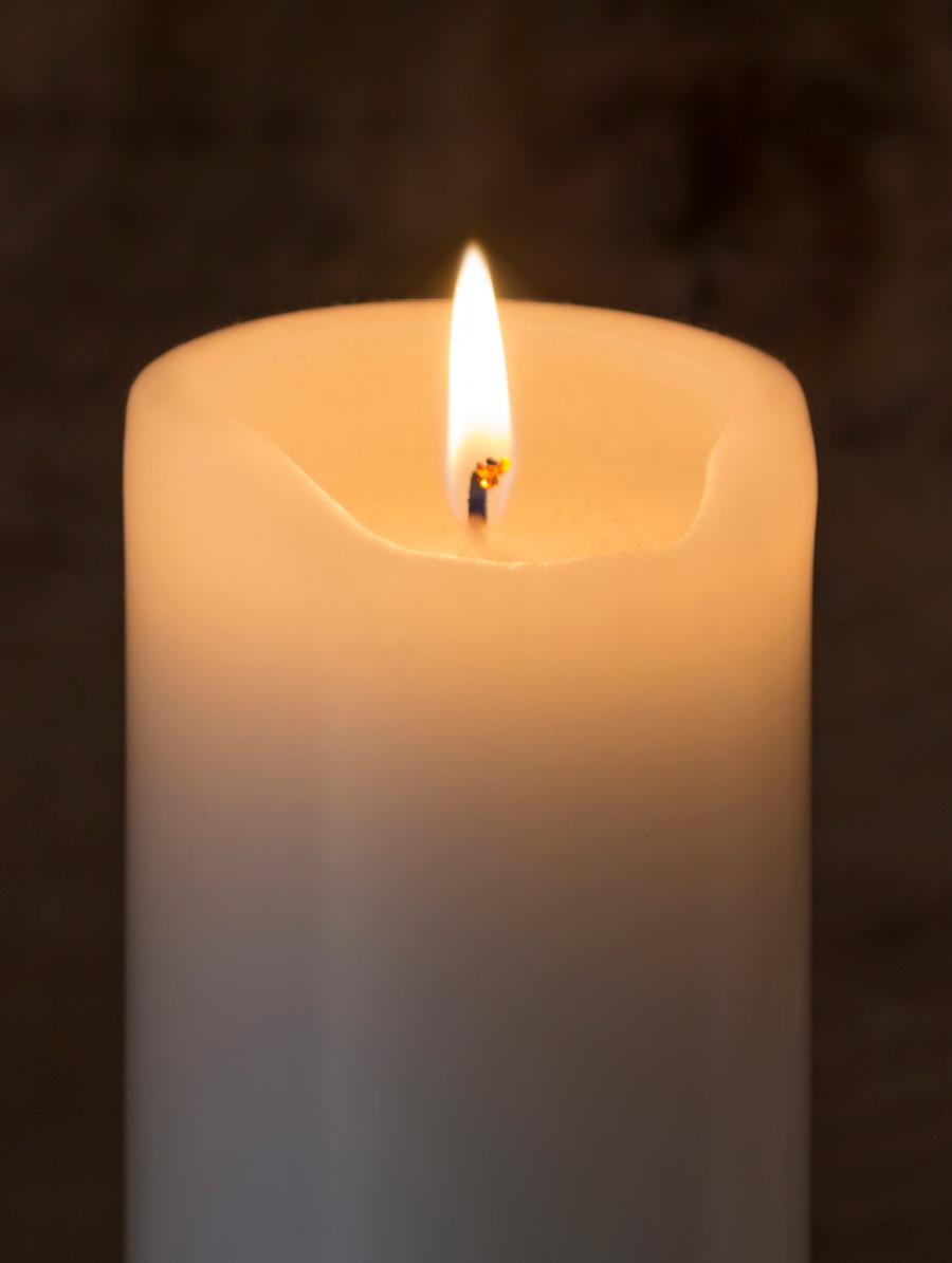 Et rundt tændt stearinlys på en mørk baggrund.