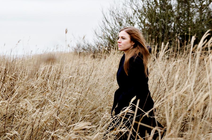 Forfatter Stine Pilgaard står i en lang sort frakke på en mark med højt korn og træer i baggrunden.