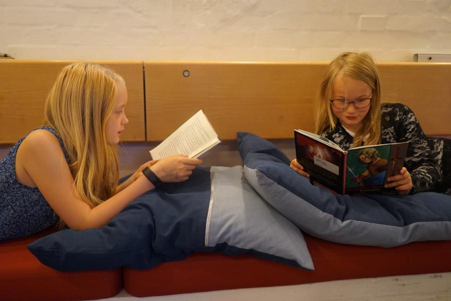 to piger ligger på puder og læser